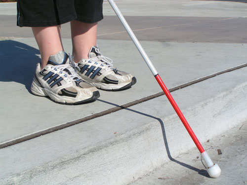 blind pedestrian with white cane waiting at curb