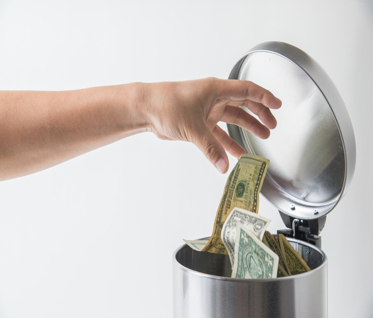 hand dropping money in trashcan