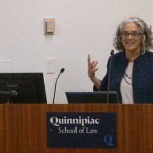 Lainey at podium with sign Quinnipiac Law School