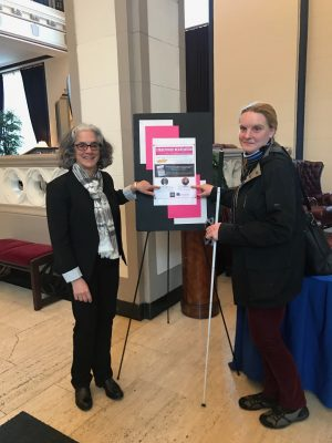 Jessie Lorenz and Lainey in front of Hastings event poster