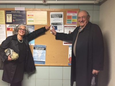 Lainey and her dad pointing to poster announcing book event at Harvard