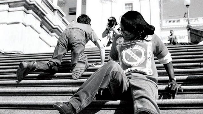three disabled people crawling up the steps of the capitol as part of a protest to get the ADA past. Black woman in foreground, white man in background