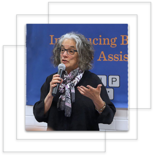 Lainey Feingold holding a microphone and speaking at an event
