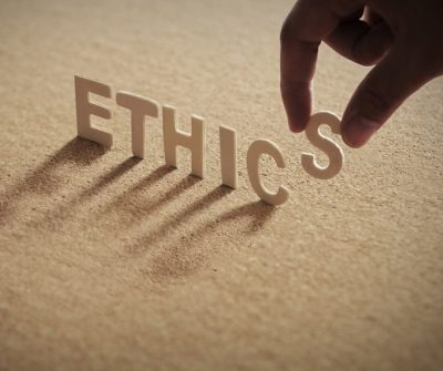 """The letters of the word """"Ethics"""" standing on a san-colored background as the final """"S"""" is placed"""